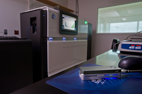 A small nanopore sequencer (about the size of a short stapler) sits on a table in the foreground. In the background is a large sanger sequencer machine (the size of a large copy machine)