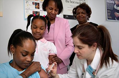 A nurse in the process of administering an intramuscular vaccination into a girl's left arm whose sister, mother, and grandmother watched from the background