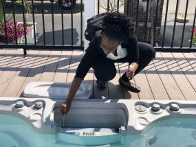 a woman kneels beside a hot tub with a swab in one hand and a sample container in the other