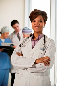 Female doctor smiling at camera with group of doctors looking over a chart in the background