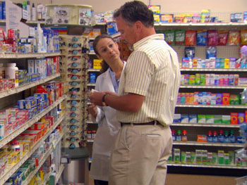 Pharmacist explaining to a customer which over-the-counter medications may help relieve his symptoms.
