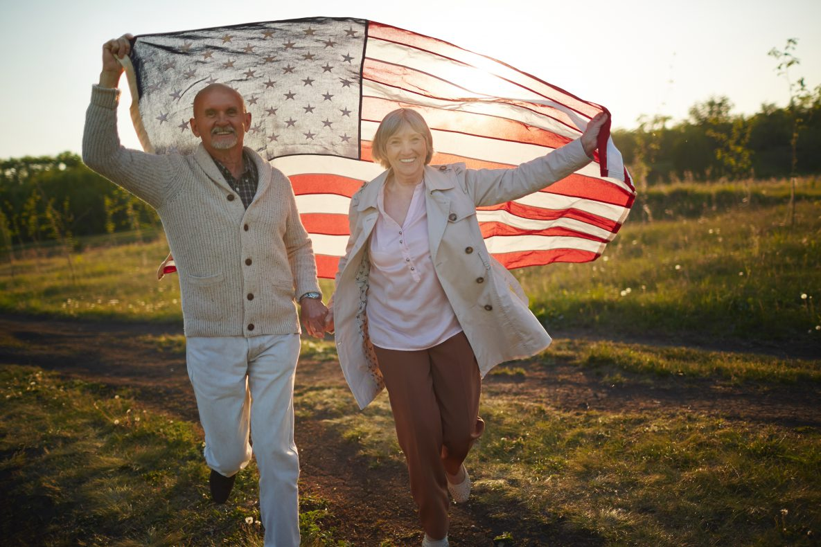Physically active male and female veteran couple raise American flag as they hold hands and jog in an open field.