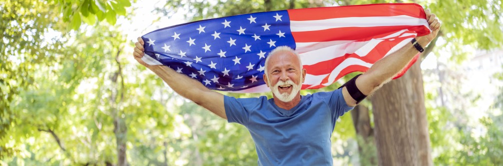Veteran raises American flag overhead in celebration while walking in the park