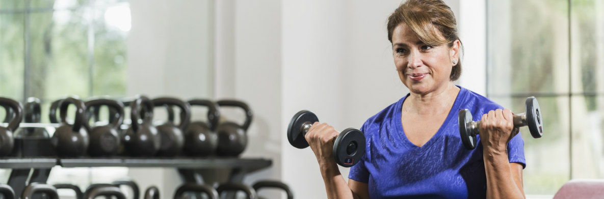latina woman lifting weights in a gym
