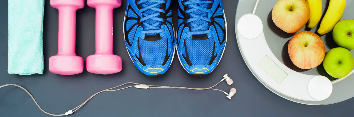 Close up of headphones, handheld weights, walking shoes, and apples and bananas.