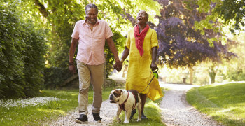 older black couple walking dog in the park