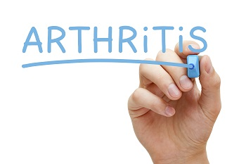 an adult hand writing the word arthritis
