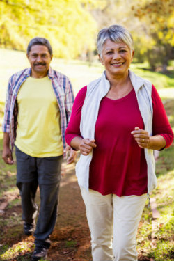 older African american man and woman walking in the park