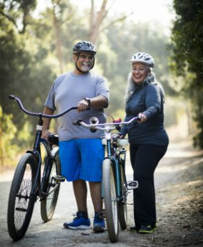 Latino man and woman standing with bicycles.