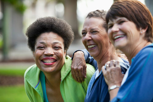 three older women laughing outdoors