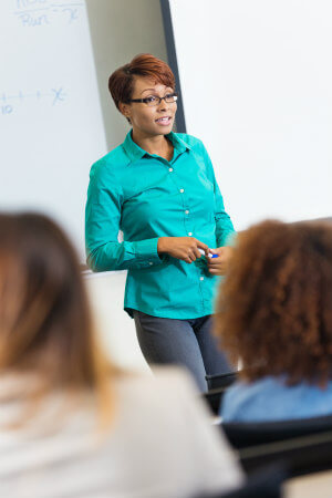 woman teaching in front of a class of adults