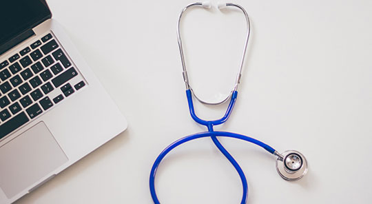 image of a stethoscope and a laptop