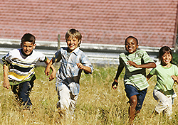 kids running through a field of tall grass