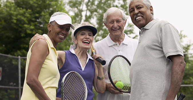 two older couples playing tennis