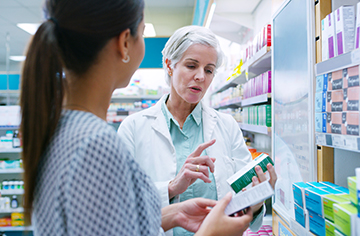Pharmacist discussing medications with a customer.