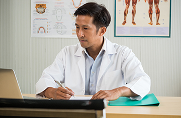 Physician looking at a computer.