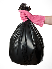 hand with pink glove and trash bag