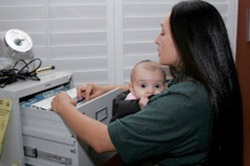Mother looking through a filing cabinet with an infant