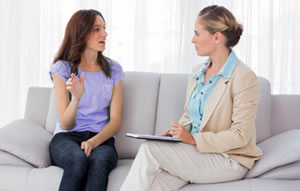 Photo of a young women talking to a genetic counselor
