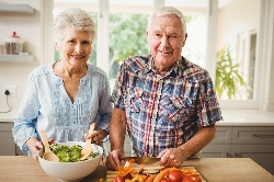 Photo of a man and a woman making a salad