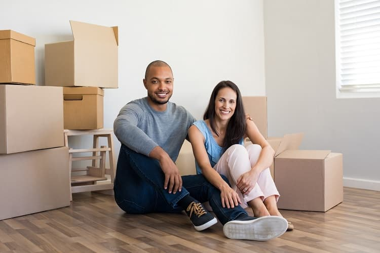 Photo of a couple sitting on the floor with boxes ready to move.