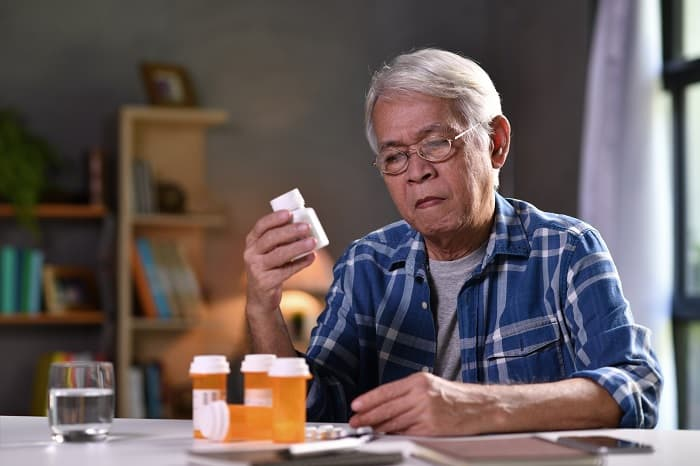Photo of a worried man with bottles of prescription medicines