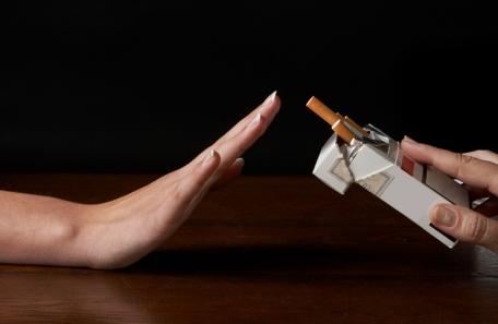 Mano empujando lejos un paquete de cigarrillos