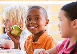 Photo of three children eating lunch. One child is eating an apple.