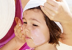 Photo of a mother applying sunscreen to her daughter's face.
