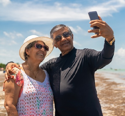 Photo of a senior couple taking a selfie on the beach