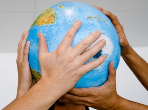 Photo of diverse hands holding a globe