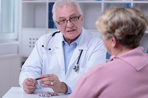Photo of a doctor prescribing antiviral drugs for a cancer survivor