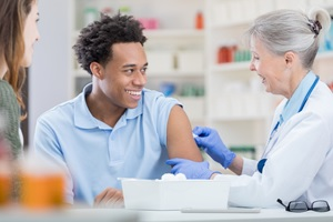 A nurse prepares to give a flu shot to a young man