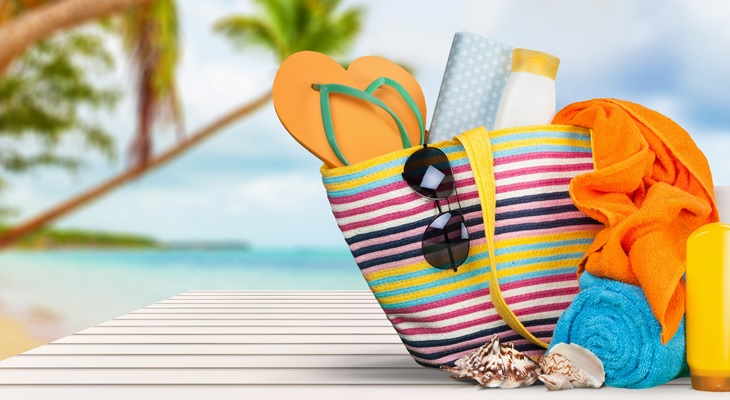 Photo of a colorful tote bag containing sunscreen, sunglasses, a hat, towels, and shoes.