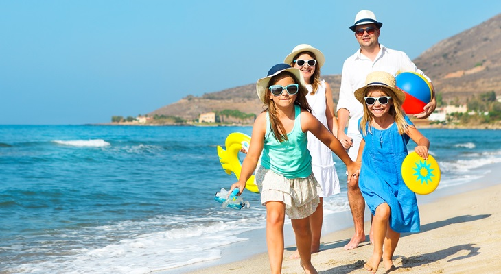 Photo of a family on the beach wearing hats and sunglasses