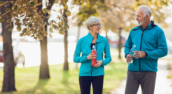 Mature couple walking together holding water bottles