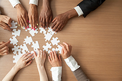 Hands of multi-ethnic business team assembling jigsaw puzzle, top view royalty-free stock photo.