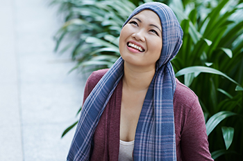 Photo of a young cancer survivor wearing a scarf around her head.