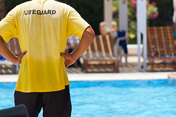 Photo of a lifeguard watching people at the pool.