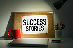 A banner with the words Success Stories pinned to a dashboard against a wall.