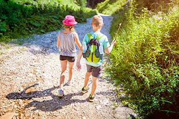 Photo of a boy and a girl walking in a mountain trail.