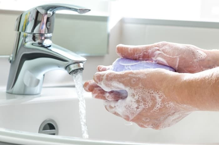 Photo of a person washing hands.