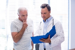 Photo of a doctor and a patient looking at his medical chart