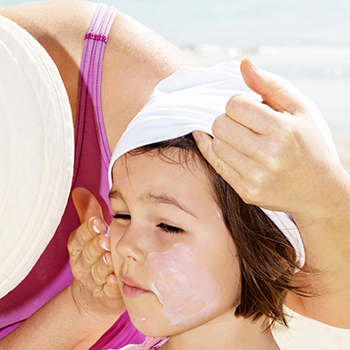Photo of a mother applying sunscreen lotion to her daughter