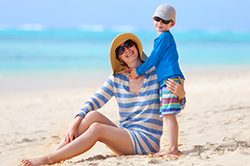 Photo of a mother and child on the beach. Both are wearing sunglasses, hats, and long-sleeved shirts.
