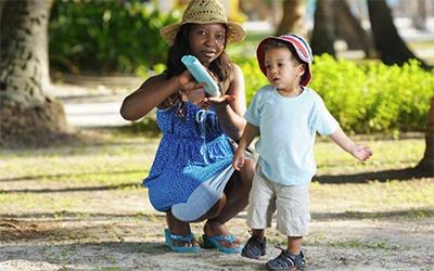Woman putting sun screen lotion to her child. Both wearing hats.