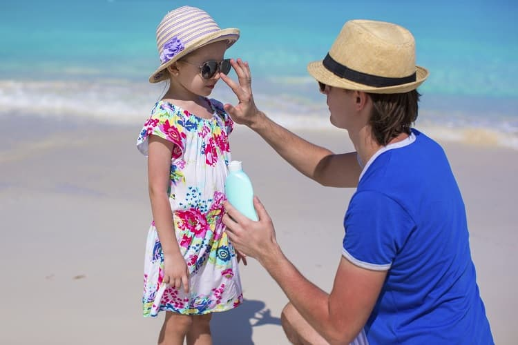 Photo of a father putting sunscreen on his young daughter