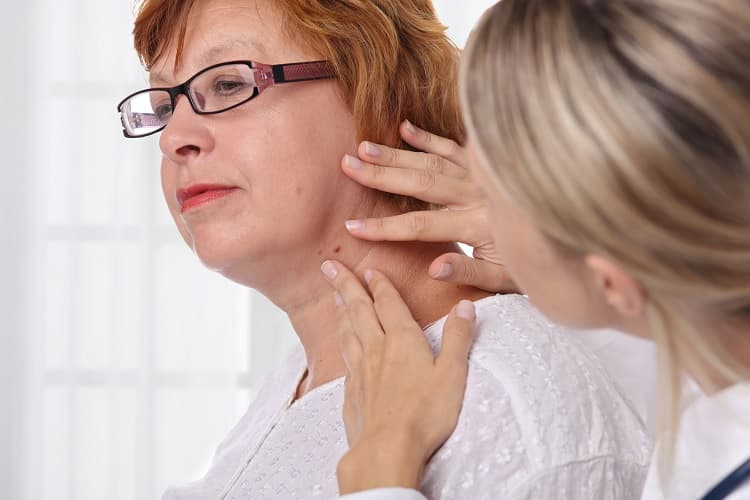 Photo of a doctor examining a mole on a woman's neck