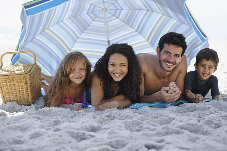 Photo of a family under a large umbrella on the beach