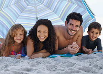 Photo of a couple with their children in the beach covered by their umbrella